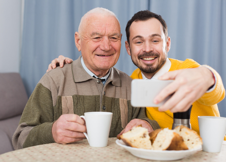 eldest: Smiling elderly father and son doing selfie at home at table