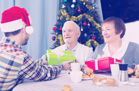 Elderly parents take gifts from son for Christmas at festive table