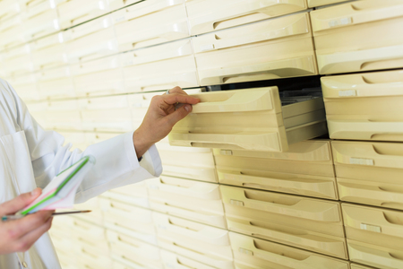 Pharmaceutical chemist opening drawer for drugs  storage  in farmacy