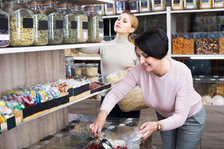 a jar stand: Cheerful young blond and mature brunette women choosing dried herbs sold by weight in organic shop