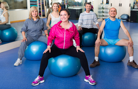 adult people stretching in a gym on fitness balls Stock Photo