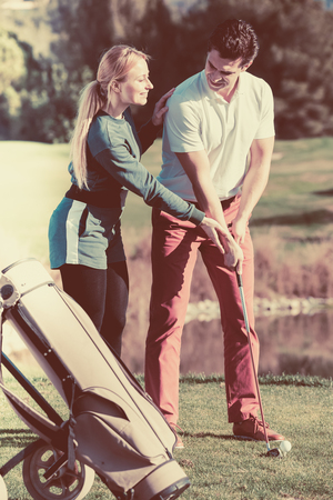 brassy: Happy golf trainer showing male player how to hit ball rightly