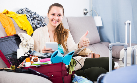 Young glad woman packing luggage for holidays at home Stock Photo