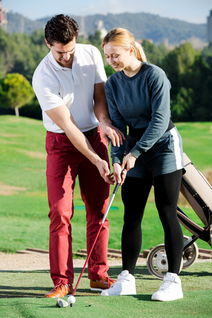 Positive male golf trainer showing female player how to hit ball rightly