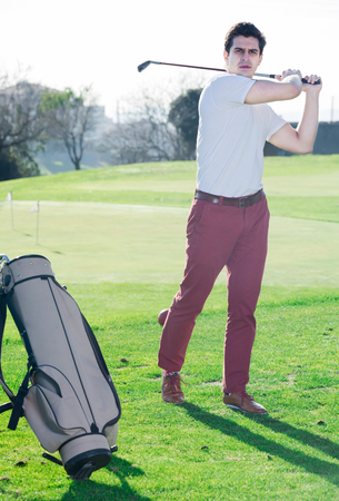 brassy: Male golfer successfully hit the golf ball looking at the result Stock Photo