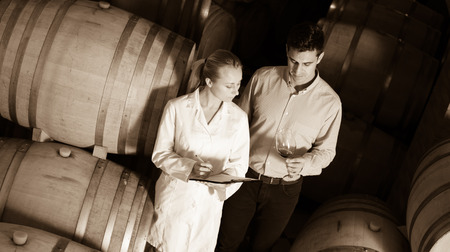 house robes: Portrait professional sommelier advising male customer in winery cellar