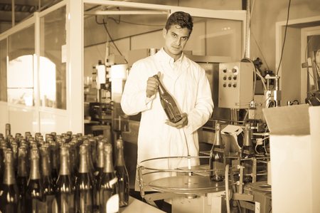 Young man holding newly produced bottle of wine on winery manufactory