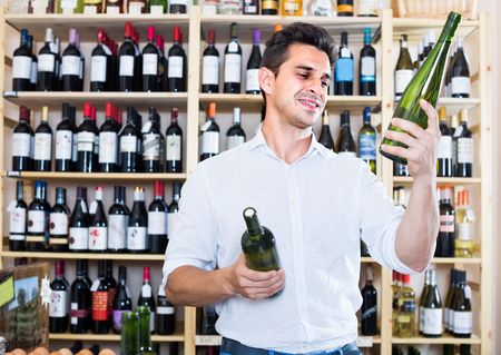 excited man  choosing  bottle of wine in store with alcohol drinks