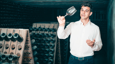 expert man holding glass with wine sample in cellar with bottles