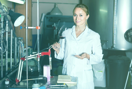laboratorian: cheerful female specialist checking wine fermentation in winery laboratory Stock Photo