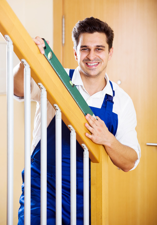 Positive handyman fixing stairway railing in new apartment Stock Photo