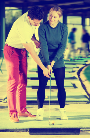 Smiling man golf trainer showing woman player how to hit ball rightly Stock Photo