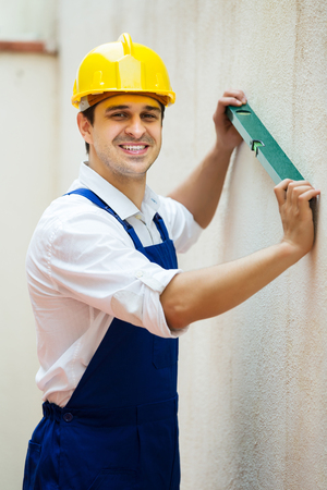 Smiling specialist making wall plane in new building Stock Photo