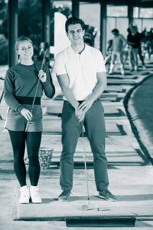 readiness: Glad male and female golfers are ready for tour of game at golf course Stock Photo