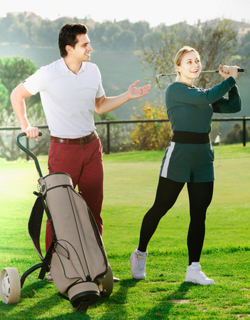 Man 30-35 years old is showing woman 25-29 years old to play golf and hit ball correctly.