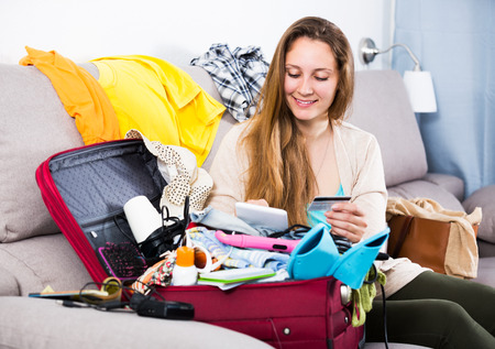 booked: Young smiling woman getting ready for holidays indoors