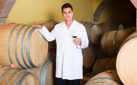 laboratorian: cheerful man in white robe checking ageing process of red wine Stock Photo