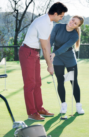 Cheerful golf trainer showing male player how to hit ball rightly Stock Photo