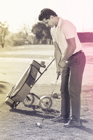 brassy: Young positive  man preparing to hit ball at golf course Stock Photo