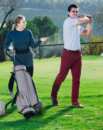 Girl and man golfers delight successful hitting the ball in the hole golf course Stock Photo