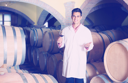 laboratorian: cheerful smiling professional taster of winery posing with wine in cellar