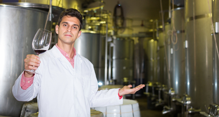 Serious male winery technician posing with wine in modern cellar