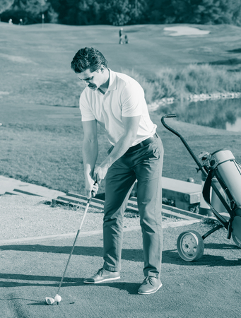 brassy: positive american man playing golf is going to hit ball at golf course