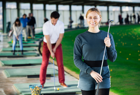 brassy: Young female golfer is ready for play at golf course