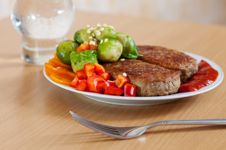 fried beefsteaks and vegetables on plate at table