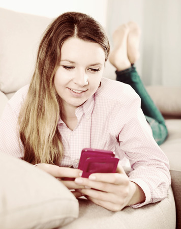 Smiling girl texting with her phone and taking photos at home