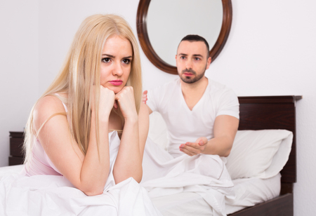 impotent: Upset young husband pleading in front of offended wife in bedroom Stock Photo