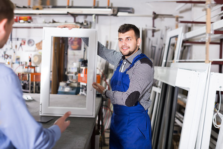 man profile: Handsome production workers in coverall with different PVC windows and doors