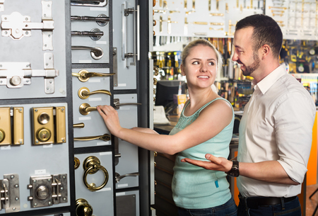 lintel: Young cheerful couple standing next to showcase with a door handles and choosing one. Focus on both persons Stock Photo