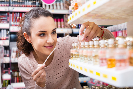 Happy young woman choosing the things for makeup and smiling in a store