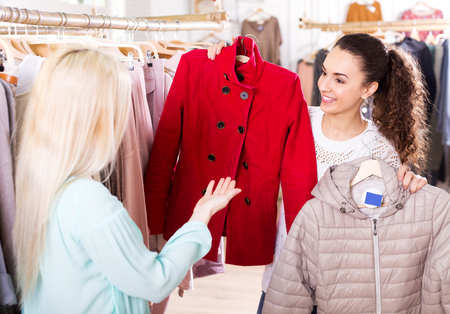 outer clothing: Positive young female customers selecting coats and jackets at the shop Stock Photo