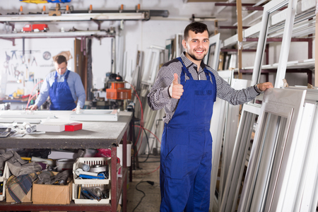 man profile: Young guy worker is inspecting the window frame in workshop. Stock Photo