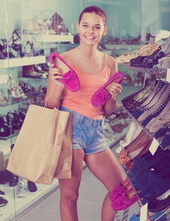 happy smiling teenager girl in shorts choosing pair of fashion shoes in boutique