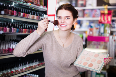 inquiring: cheerful woman customer deciding on compact powder in cosmetics shop Stock Photo