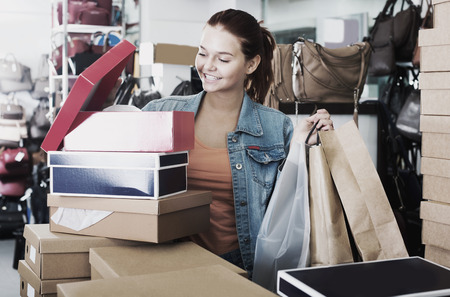 consuming: Happy girl looking into boxes with new pairs of shoes in fashion shop