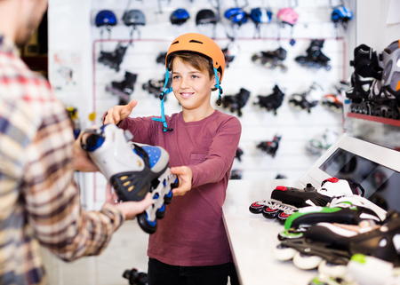 happy male shop assistant helping positive boy to choose roller-skates in sports store Stock Photo