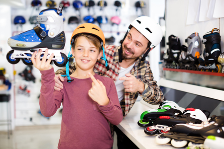 boasting: Positive father and son boasting purchased roller-skates in sports store