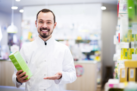 prescribed: Glad male pharmacist offering reliable medicine in drugstore Stock Photo