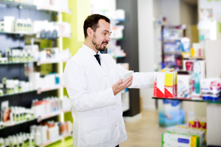 prescribed: Young man pharmacist searching for reliable drug in pharmacy Stock Photo