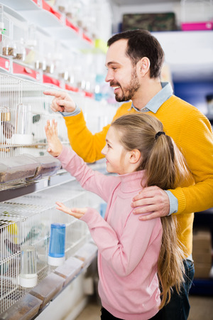 Father with his daughter treated parrots and canaries in a pet shop Stock Photo
