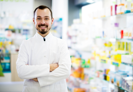Man pharmacist displaying assortment of drugs in pharmacy Stock Photo