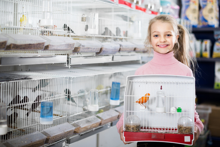 Smiling girl customer purchased purchase of canary bird in pet store Stock Photo