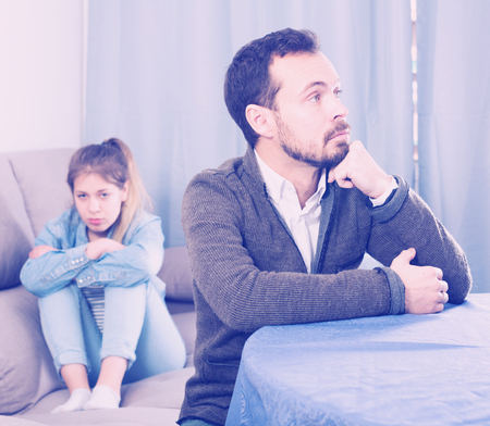Young father having disagreement with daughter teenager at home