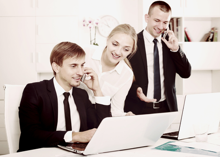 Cheerful business male and female assistants in formalwear working on laptops and talking on mobile phone in firm office