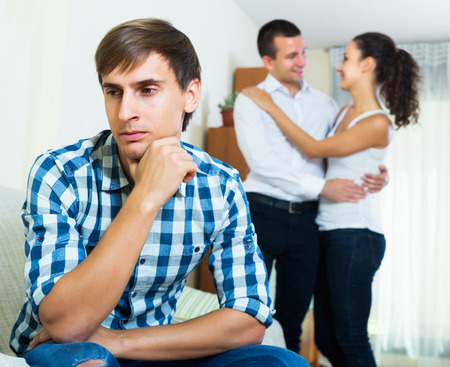 Unhappy ex-lover watching happy girlfriend leaving him for another man