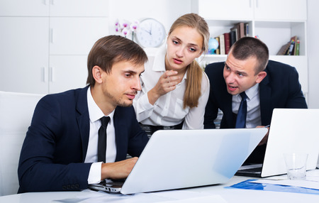 fiasco: three upset coworkers experiencing business failure in firm office Stock Photo